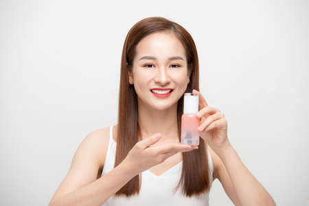Young Asian woman holding cosmetics product, bottle over white background. 免版税图像