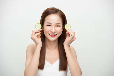 Beautiful joyful Asian woman posing with cucumber and smiling isolated over white background