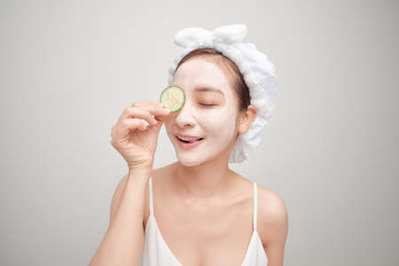 Attractive young woman covering her eyes with cucumbers on a blue background. Clay mask. 免版税图像 - 164880812