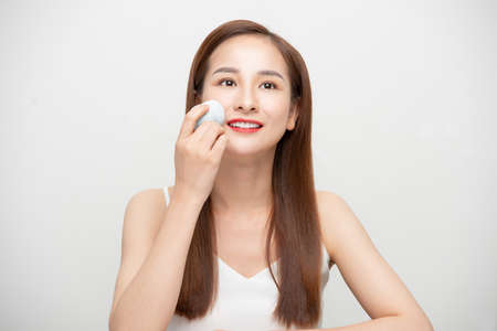 Beauty portrait of a lovely young woman  isolated over white background, using makeup sponge 免版税图像