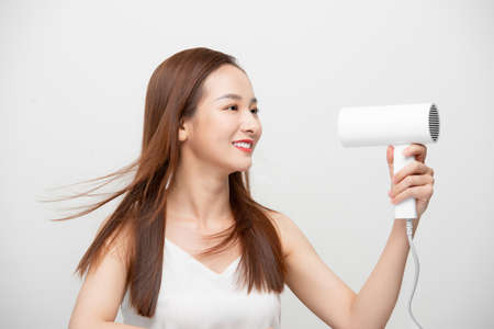 Attractive beautiful Asian woman blowing the wind by hair dryer 免版税图像