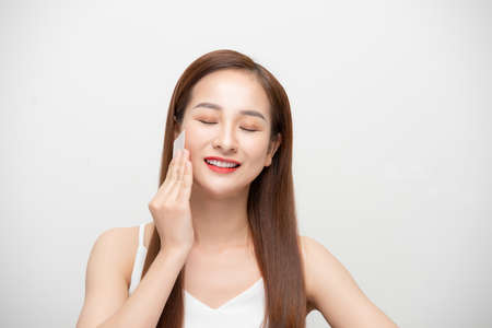 Face skin care. Smiling Asian woman using facial oil blotting paper portrait 免版税图像