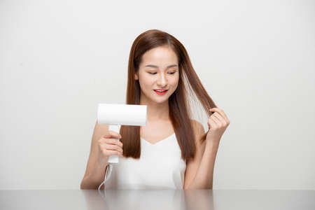 Asian woman uses hair dryer on white background.