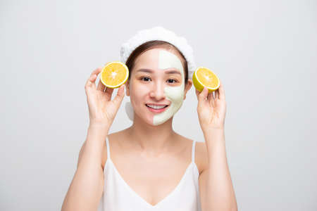 Pretty Asian young woman mask moisturizing and rejuvenating clean skin peeling while holding orange pieces over white background. 免版税图像