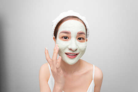 Beauty Face Care. Portrait Of Young Asain Girl Touching Her Perfect Soft Facial Skin. Over white background. 免版税图像