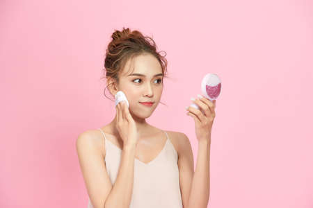 Woman hold cushion face foundation case with hands while apply foundation on the face by herself.