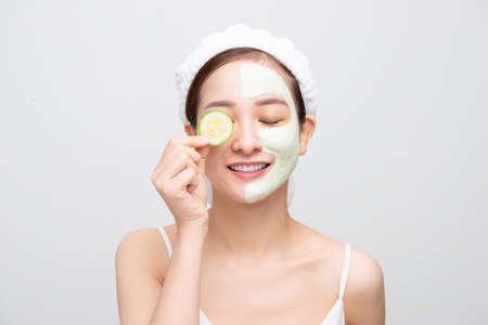 Attractive young Asian woman with clay mask and holding fruit piece isolated over white background. Beauty concept. 免版税图像