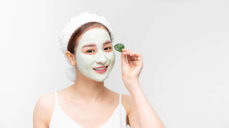 Beauty portrait of Asain woman in towel on head with white nourishing mask on face and green leaf in hand, white background isolated. Skincare cleansing eco organic cosmetic spa concept