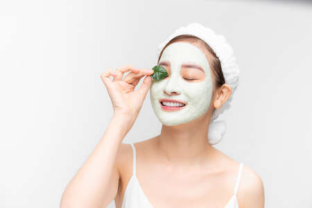 Portrait beautiful Asian woman in towel on head applying white nourishing mask or creme on face, green leaf in hand isolated white background 免版税图像