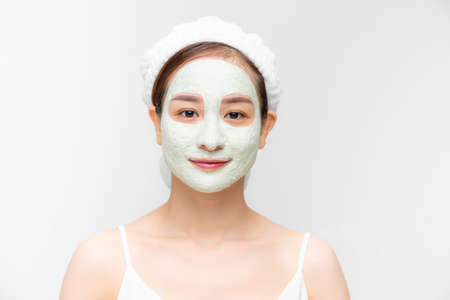 Portrait of beautiful young Asian woman with clay mask and towel on her hear over white background.