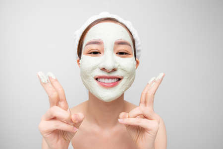 Woman with purifying mask on her face isolated on white background