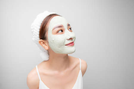 Attraactive young Asian woman with a face clay mask against acne on the face of a woman to rejuvenate the skin