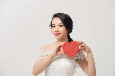 Portrait of young beautiful Asian girl holding love gift box over white background. 免版税图像