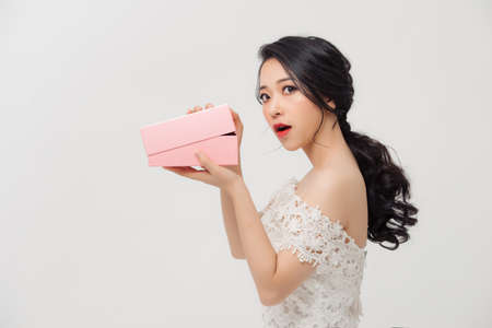 Amazed young Asian woman opening the pink gift box over white background.