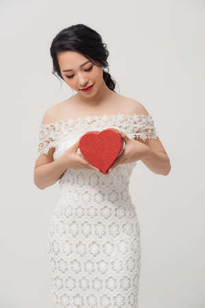 Beautiful young Asian woman holding love gift box isolated over white background.