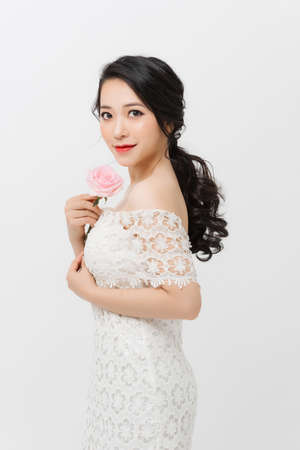 Attractive elegant Asian woman holding flower and wearing white dress over white background. 免版税图像 - 164704421