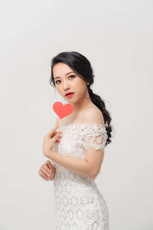 Elegant Asian woman holding a parper heart and standing isolated over white background.