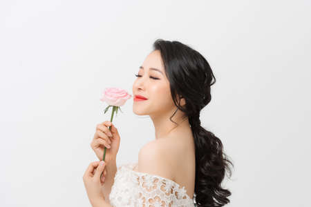 Attractive elegant Asian woman holding flower and wearing white dress over white background.