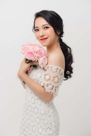 Beautiful happy Asian woman wearing white dress and holding flower rose bouquet over light background. 免版税图像 - 164704431