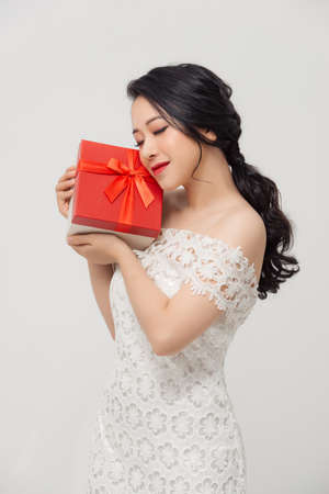 Happy young elegant Asian woman holding special gift box and wearing dress over white background.