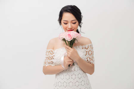 Happy Asian young attractive woman holding flower bouquet and wearing white background.