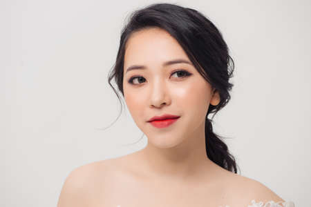 Portrait of young elegant Asian woman with white dress isolated on light background.