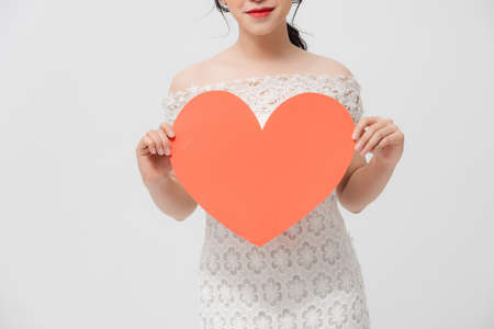 Attractive young Asian woman holding red love shape and standing over white background.