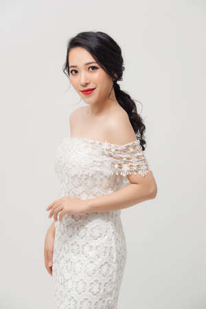 Beautiful Asian young woman in white dress posing on the white background. Beauty, fashion. Haircare. Cosmetics. 免版税图像