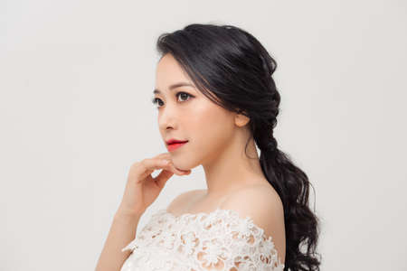 Portrait of young elegant Asian woman with white dress isolated on light background. 免版税图像 - 164880835