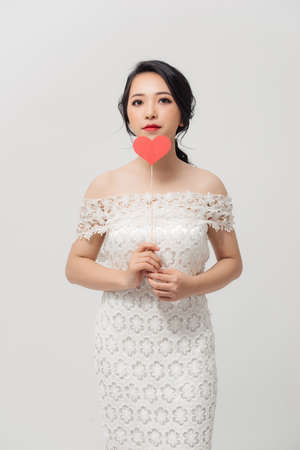 Happy young Asian woman holding love sign over white background.