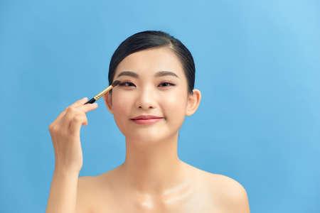 woman applying eyeshadow on eyelid using makeup brush Stock Photo