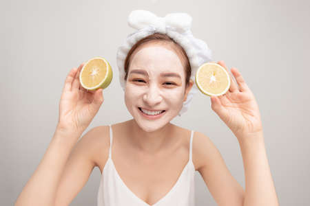 portrait of pretty young woman with clay mask on her face holding slices of orange, facial care Standard-Bild