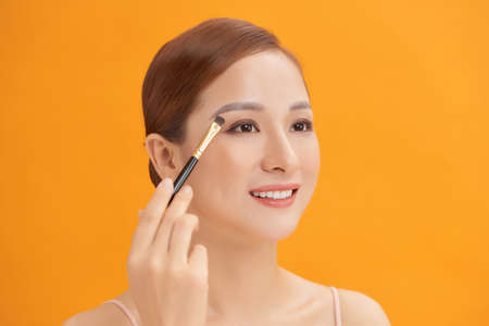 Beautiful woman using brush for eyeshadow. Photo of woman with perfect makeup on yellow background. Beauty concept