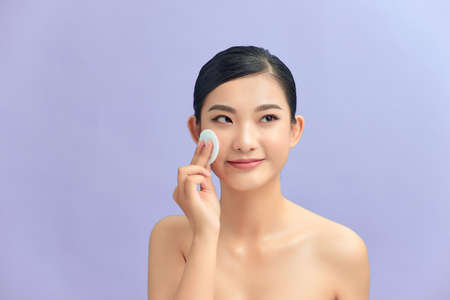 Crop attractive young female cleansing face with a cotton pad on a purple background in studio Standard-Bild