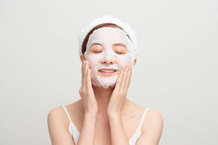Closeup portrait of young pretty woman applying paper sheet mask on her face. Cosmetic procedure. Beauty spa and cosmetology. Zdjęcie Seryjne