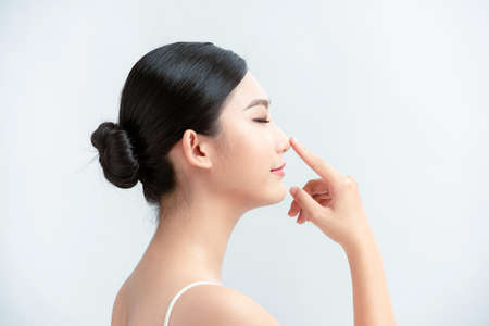 beauty skincare woman smile happily and pointing her nose on white background Foto de archivo