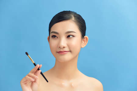 Beautiful woman using brush for eyeshadow. Photo of woman with perfect makeup on blue background. Beauty concept