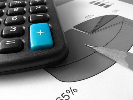 A blue big sum key of a calculator on a black and white photo of three piles of coins of dollars and a pen over a background of pie, bar and line graphs Stock Photo - 1908019