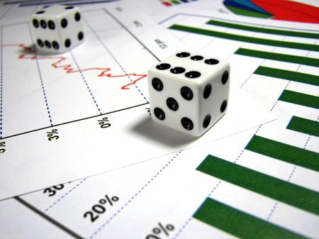 A close up on two white dice over several graphs that are of different types. The main light is focused on the front die. Stock Photo - 1979528