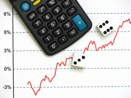 A calculator besides two dice on top of a stock market graph of increasing trend