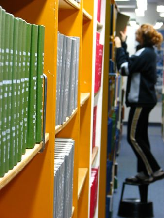 books on a shelf and a woman on top of a step reaching for a book, shallow depth of field, focus on the nearby books