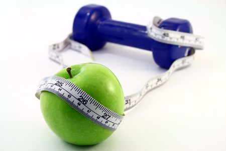 a green apple with a measuring tape wrapped around it in front of a blue dumbbell, isolated in white