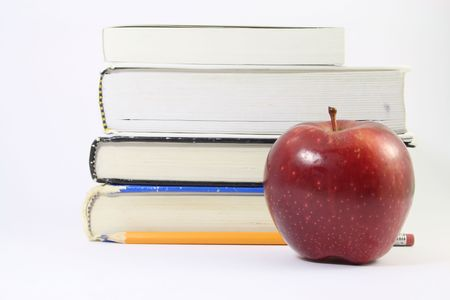 fresh graduate: A red apple in front of several textbooks and an yellow pencil, isolated on white