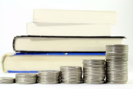 Several piles of silver coins with increasing height in front of several textbooks, isolated on white. Increasing cost of education. Stock Photo
