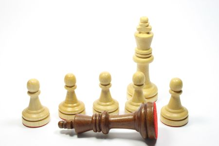 Chess pieces - Five white pawns  a king and a tipped black king photo
