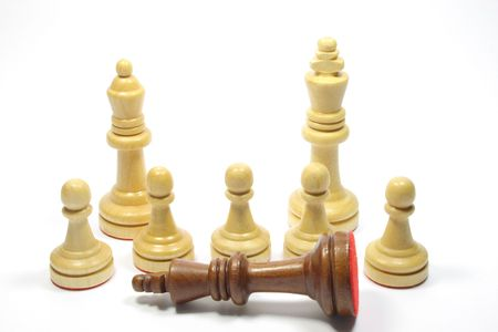 Chess pieces - Five white pawns  a king a queen and a tipped black king photo