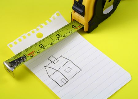 a measuring tape over a drawing of a house on a notepad