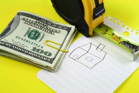 a measuring tape and several folded one hundred dollar bills over a drawing of a house on a notepad Stock Photo