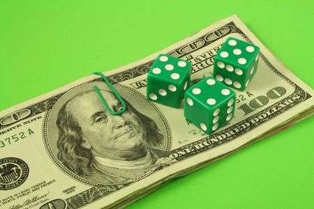 three green dice over several bills of one hundred dollars Stock Photo - 2173749