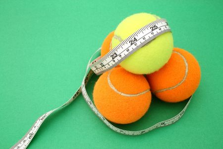 tape measure wrapped around four tennis balls photo